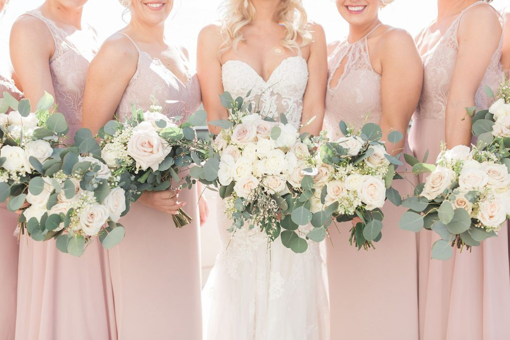 Budget Brides - Just Marry Weddings - Personal Floral - Bride holding up her white and blush bouquet with her bridesmaids beside her holding their matching bouquets